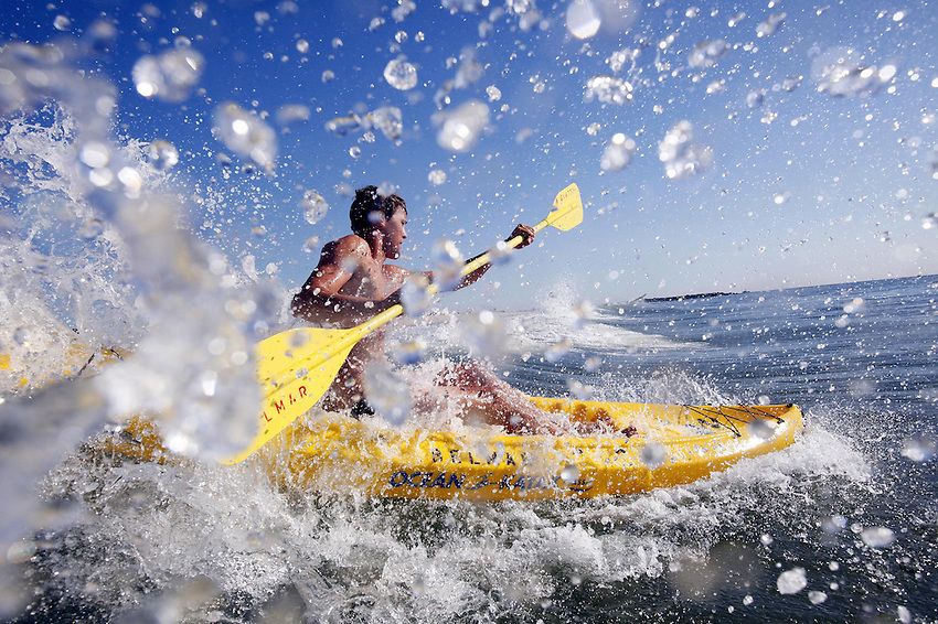 BELMAR, NJ Lifeguard Greg MacDonald punches an ocean kayak through a breaking wave during an early morning workout with the Belmar Beach Patrol as they prepare to host next week's Howard Rowland Memorial Lifeguard Tournament. (7/1/2010)