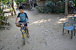 Eleven-year old Juan Lopez rides his bike at his home in Zipolite, a town in Oaxaca, Mexico. Juan is blind, and yet rides his bike to school with his sister's help. She perches on the back and signals him which way to steer by pinching his shoulder. If she pinches his right shoulder, for example, he goes right. The harder the pinch, the sharper the turn.