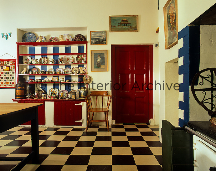 This country-style kitchen has been given a paint over, with blue and white striped walls and red gloss woodwork as a counterbalance to the black and white checked lino