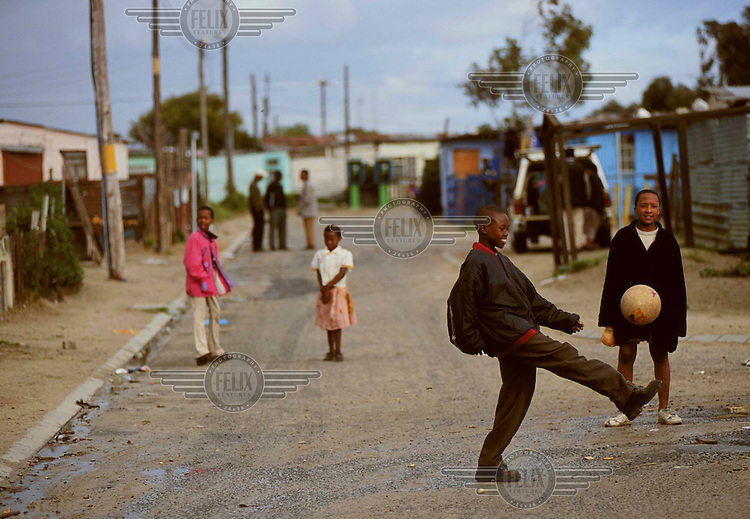 Children play football in the streets of Khayelitsha Township.