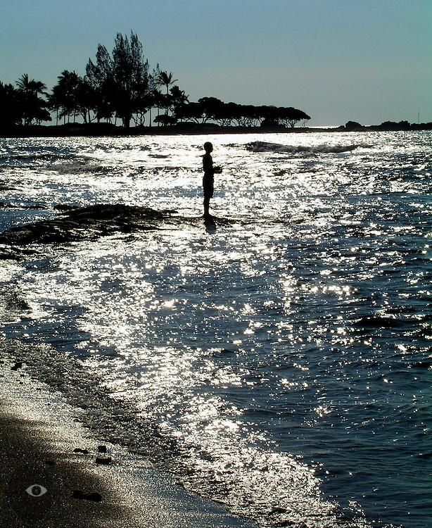 A fisherman takes in the sun and surf along the kohala for Fishing big island hawaii