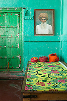 The mixture of greens in the decoration of this haveli bedroom enhances the pattern of a length of Osborne & Little fabric on the wooden bed