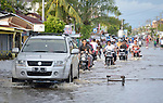 Cars and motorbikes traverse inundate streets during November 2014 flooding in Meulaboh in Indonesia's Aceh province. Flooding in the region has grown worse because of climate change and the proliferation of palm oil plantations.