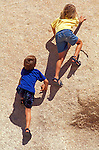 Kids (ages 4 & 8) climbing on granite boulder, Joshua Tree National Park, California USA