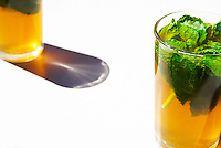 Two glasses of Moroccan mint tea, with fresh mint leaves, on a white cafe tabletop in Sefrou, Morocco.