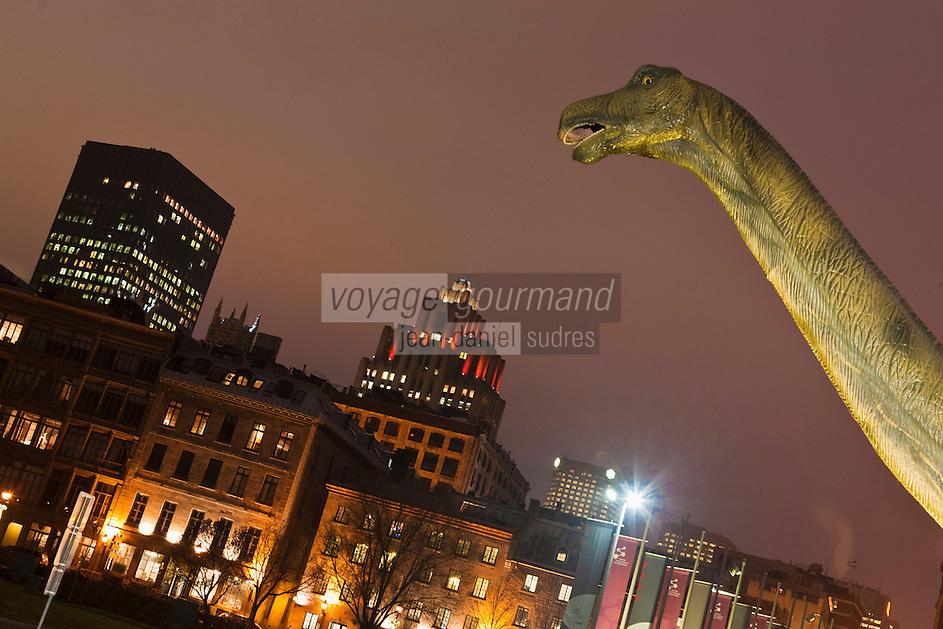 Amérique/Amérique du Nord/Canada/Québec/Montréal: Lors d'une exposition sur les Dinosaures au  Centre des sciences de Montréal . Tête de Dinosaure et le Vieux-Montréal et les Gratte ciel