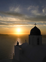 The outline of an ancient church in Santorini, Greece in silhouette against the setting sun over the Mediterranean
