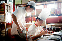 A chef completes paperwork in one of the kitchens at The West Lake Restaurant. Able to seat up to 5,000 people at one sitting, The West Lake Restaurant is the biggest Chinese restaurant in the world. Each week its diners, who staff are taught are 'the bringers of good fortune', devour 700 chickens, 200 snakes, 1,200 kgs of pork and 1,000 kgs of chillis. Its 300 chefs cook in five kitchens and its staff total more than 1,000.It is fully booked most nights.