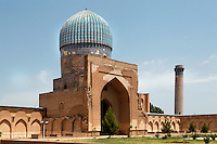 General view of one of the three smaller domed buildings with one of the corner minarets of the front (east) facade, Bibi-Khanym Mosque, 15th century,  Samarkand, Uzbekistan, pictured on July 16, 2010, in the morning. Named after the wife of Amir Timur, 14th century ruler, the mosque was constructed following his 1399 Indian campaign. It collapsed after an earthquake in 1897 and was restored in the late 20th century. Samarkand, a city on the Silk Road, founded as Afrosiab in the 7th century BC, is a meeting point for the world's cultures. Its most important development was in the Timurid period, 14th to 15th centuries. Picture by Manuel Cohen.