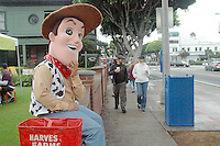 People walk past Christopher Andrews in a Woody (Toy Story) costume at the Santa Monica Farmers Market on Sunday, October 17 , 2010. Woody was promoting Robinsen Beautilities Halloween Headquarters. .