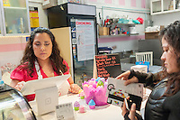 Owner Tabatha Lozano waits on customers using an iPad equipped with Square payment technology at the Sprinkle Splash Sweet Shoppe, the newest addition to the shops located in La Marqueta in East Harlem in New York, seen on its opening day, Saturday, April 2, 2016. Besides the incubator kitchen in the building there are a number of retail spaces in the revitalized facility rented by the entrepreneurs and small businesses which use the kitchen. (© Richard B. Levine)