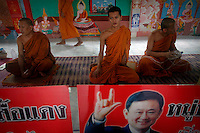 Buddhist monks sit behind picture of ousted premier Thaksin Shinawatra during a religious ceremony at a temple in the village of Suan Mon near Udon Thani in northeastern Thailand June 25, 2011. Saffron-robed monks chanted and young women in silk sarongs stretched out their arms in traditional Thai dance moves, but the big event was the voice on a scratchy telephone line from another continent. ?Be prepared. Good things are about to come,? billionaire former prime minister Thaksin Shinawatra said from his Dubai mansion in a telephone call to a Buddhist temple where 38 communities declared their allegiance to Thaksin, formally becoming ?Red Shirt Villages? in solidarity with the red-shirted movement that backs him. The red shirts, supporters of ousted premier Thaksin Shinawatra, have been branding hundreds of villages as red to rally behind Thaksin's sister, Yingluck, who is leading the opposition ahead of July 3 general elections. Picture taken June 25, 2011. TO GO WITH THAILAND-ELECTION/THAKSIN REUTERS/Damir Sagolj (THAILAND)