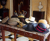 A collection of hats is displayed on a marble topped table in the entrance hall