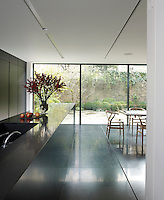 The kitchen/dining area is furnished with black lacquered cupboards and black granite work surfaces and floors