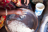 Nitu (not her real name), kneads dough in her kitchen in Jhaju village, Bikaner, Rajasthan, India on 4th October 2012. Now 18, she was married off at age 10 to a boy of around the same age, but only went to live with her in-laws when she was 12, after she had finished studying up to class 6. The three sisters, aged 10, 12, and 15 were married off on the same day by their maternal grandfather while their father was hospitalized. She was abused by her young husband and in-laws so her father took her back after hearing that her husband, who works in a brick kiln, was an alcoholic and was doing drugs and crime. She had only spent a few days at her husband's house at that time. Her father (now out of the hospital) has said that she will only be allowed to return to her husband's house if he changes his ways but so far, the negotiations are still underway. Photo by Suzanne Lee for PLAN UK