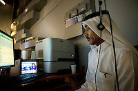 The floor manager looks on as newsreader Eman Banourah is on air for news channel Al Jazeera in Doha.