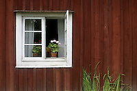 Open window with flowers in a red painted old house, part of Skansen, the first open air museum and zoo in Sweden, and is located on the island Djurgården