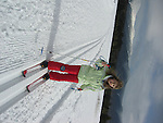 Hatless girl and gloveless girl in lime green jacket and red ski pants, cross country skis on a sunny field, with snow-capped White Mountains behind her.
