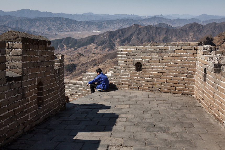 A visitor rest at the partly-restored part of Mutianyu Great Wall which lead to Jiankou Great Wall.