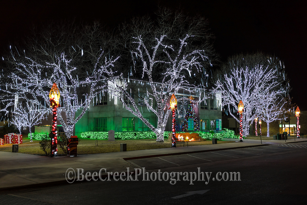 Burnet County Court house at Christmas with the holiday decorations at the town square. There are dripping lights off the trees and a nativity scene along with a large christmas tree along with other holiday lights for a festive  feel.