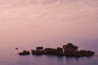 A band of rocks marks the edge of open ocean near Marino Rocks, South Australia. At sunset the ocean is pink and purple.