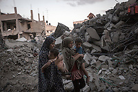 "In this Saturday, Aug. 16, 2014 photo, Palestinian women walk along rubble as they look for their belongings after airstrikes and artillery shelling hit the neighborhood during the ""Protective Edge"" Israeli military operation in Beit Hoanoun, Gaza City. After a five days truce was declared on 13th August between Hamas and Israel, civilian population went back to what remains from their houses and goods in Gaza Strip. (Photo/Narciso Contreras)"