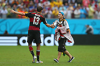 A pitch invader is shown off the field as he shakes hands with Thomas Muller of Germany