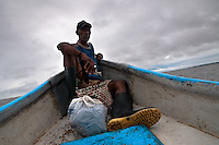 A Colombian shellfish picker sits in the head of a canoe while going to the mangrove swamps on the Pacific coast, Colombia, 12 June 2010. Deep in the impenetrable labyrinth of mangrove swamps on the Pacific seashore, hundreds of people struggle everyday, searching and gathering a tiny shellfish called 'piangua'. Wading through sticky mud among the mangrove tree roots, facing the clouds of mosquitos, they pick up mussels hidden deep in mud, no matter of unbearable tropical heat or strong rain. Although the shellfish pickers, mostly Afro-Colombians displaced by the Colombian armed conflict, take a high risk (malaria, poisonous bites,...), their salary is very low and keeps them living in extreme poverty.