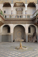 Courtyard of the Harem, Glaoui Palace, early 19th century, in Fes, Fes-Boulemane, Northern Morocco. The room has a central fountain, zellige tilework and a carved balcony which is damaged and in need of restoration. Thami Glaoui, Pasha of Marrakech, used this as his Fes residence. The complex consists of 30 fountains, 17 houses, 2 hammams, an oil mill, a mausoleum and cemetery, a madrasa, gardens and stables. Picture by Manuel Cohen