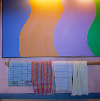 A colourful modern painting hangs on a long wall of the mudroom with woollen shawls draped over a pine pole beneath