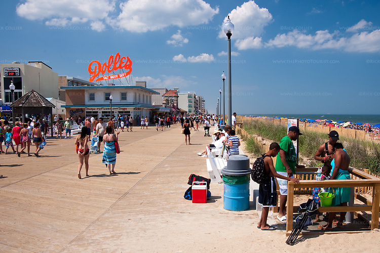 A group of beachgoers rinse the sand off at a public rinse station along the boardwalk at Rehoboth Beach, Delaware, USA.