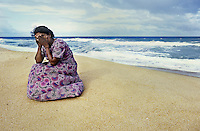 Mother who lost her three children to the sea when the tsunami hit   <br /> Batticola, Sri Lanka<br /> Of the 8,000 residents of Batticaloa, 5,000 died. That&rsquo;s 60 percent of its population. The once-thriving beach-front village was surrounded by a lagoon so there was nowhere to run when the giant wave hit, just into more water. Saris and clothing were left embedded in the barbed wire set up to protect against wild animals, where many of the bodies were trapped in its grip. A few remnants were scattered: cooking pots, photographs with cracked glass, clocks stopped when the wave hit at 9:22, Buddhist statues which mysteriously remained standing. But mostly there was just rubble. Everywhere had its own ghosts. <br /> &lt;indnt&gt;I viewed the beach, cluttered with personal effects. Human bones had started to wash up. A woman walked alongside me who appeared to be in shock. As I turned to ask if she was all right she began madly gesticulating toward the sea, indicating that it had taken her two children. She, as so many I encountered, now lived with the image of seeing her family swept away and struggled with the profound guilt of being unable to hold onto her children. Beside herself with anguish she attempted to throw herself into the ocean. I pulled her back and held her as she wept. Inconsolable, she buried her face in the sand. Death is certainly more integrated with life in this part of the world, but there was no quantifying the universality of a mother&rsquo;s pain.