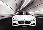 White 2014 Maserati Ghibli S Q4 luxury car speeding in a tunnel. Front view.