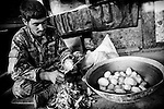 An Afghan soldier peals potatoes at Observation Post Mace, near Gowerdesh in northern Kunar, 27 November 2011. (John D McHugh)