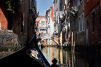 Gondola passing under a bridge on a narrow canal between buildings, Venice, Italy. Many of the houses and palazzos fronting the canals are in Venetian Gothic style, a style originating in the 14th century and combining Gothic lancet arches with Byzantine and Moorish influences. The city of Venice is an archipelago of 117 small islands separated by canals and linked by bridges, in the Venetian Lagoon. The historical centre of Venice is listed as a UNESCO World Heritage Site. Picture by Manuel Cohen