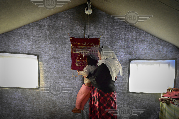 Bahar, a Yazidi woman, holds her daughter Suham up to a religious wall hanging to kiss inside their tent in a Yazidi refugee camp in the Sinjar mountains. <br /> Thousands of Yazidis fled to the mountains when Islamic State (IS) fighters attacked towns and villages around Sinjar in August 2014. Since then Yazidi refugees have been living in precarious conditions with no electricity or running water and children haven't been attending school. Support from the international community has been insufficient and people are dying of hunger and disease. Until December 2014 the mountains were surrounded by IS. Now the southern part of the mountains is still under IS control.