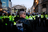 A punk with a Mohican stands in front of riot police outside the Bank of England as thousands of protestors descended on the City of London ahead of the G20 summit of world leaders to express anger at the economic crisis, which many blame on the excesses of capitalism.