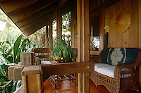 The cool veranda of a house in the tropics designed by Oscar de la Renta is surrounded by lush vegetation and palm trees