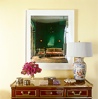 A contemporary photographc print is displayed above an antique hall table and a collection of vintage silver