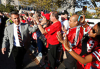 Ohio State Buckeyes head coach Urban Meyer high fives fans as the team makes their way to the stadium before the NCAA football game between the Ohio State Buckeyes and the Wisconsin Badgers at Ohio Stadium in Columbus, Saturday evening, September 28, 2013. (Columbus Dispatch  / Eamon Queeney)