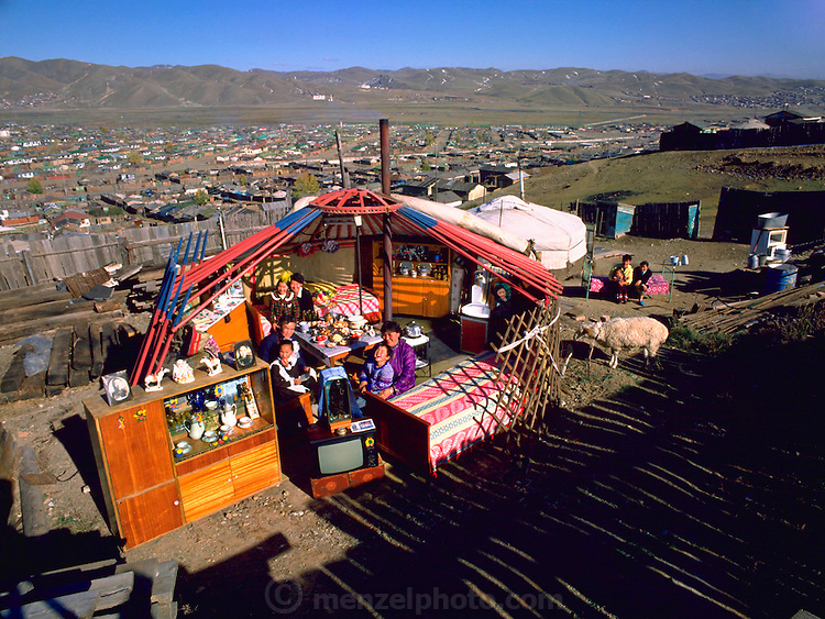 Mon.mw.01.xxs..The Regzen family outside their ger with all of their possessions, Ulaanbaatar, Mongolia. Published in Material World pages 40-41. The Regzen Batsuuri family lives in a 200 square foot ger (round tent built from canvas, strong poles, and wool felt) on a hillside lot overlooking one of the sprawling valleys that make up Ulaanbaatar, Mongolia. They live in a squatter's area, as do thousands of other Mongols who moved here from the rural countryside. There is no infrastructure in the area so electricity is cabled in illegally. {{Family members must walk to a community well to pump water and bring it home for laundry, cooking, and washing. Oyuntsetseg is a pharmacist who began her career working in a government pharmacy.}} Regzen Batsuuri is a truck driver..Family members are: Regzen Batsuuri (37, father); Oyuntsetseg Lhakamsuren (31, mother); Khorloo Batsuuri (9, daughter); Batbileg Basuuri (5, son), Oyunjargal Batsuuri (33, Regzen's sister); Yeruultzl Batsuuri (12, Oyunjargal's daugher). {{On the same lot, in a smaller ger, live the family of Oyuntsetseg's sister with her husband and toddler son. From Peter Menzel's Material World Project that showed 30 statistically average families in 30 countries with all their possessions.}}.