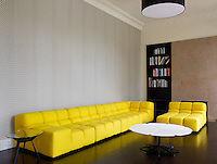 The living room is furnished with a bright yellow sofa and a patterned wallpaper by Eley Kishimoto