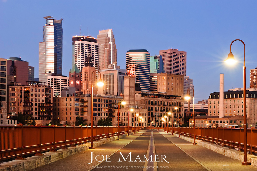 Minneapolis skyline at dawn as seen from the Stone Arch Bridge...The Stone Arch Bridge is a former railroad bridge crossing the Mississippi River at Saint Anthony Falls in downtown Minneapolis, Minnesota...Positioned between the 3rd Avenue Bridge and the I-35W Saint Anthony Falls Bridge, the Stone Arch Bridge was built in 1883 by railroad tycoon James J. Hill for his Great Northern Railway, and accessed the former passenger station located about a mile to the west, on the west bank of the river. The structure is now used as a pedestrian and bicycle bridge. It is an Historic Civil Engineering Landmark, and was added to the National Register of Historic Places in 1971 as a part of the Saint Anthony Falls Historic District, (District #71000438).