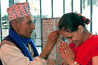 Kathmandu, Nepal.  A Hindu Priest Blesses a Worshiper by Applying a Tika of Rice and Sindur Powder to the Forehead in a Temple Dedicated to the God Hanuman.