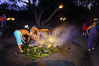 Two men remove the ti leaves and check the roasted pig for a luau at the Kona Village Resort on the Big Island of Hawaii.