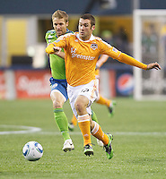 Houston Dynamo forward Will Bruin dribbles the ball up field in front of Seattle Sounders FC forward Jeff Parke during play Qwest Field in Seattle Friday March 25, 2011. The match ended in a 1-1 draw.