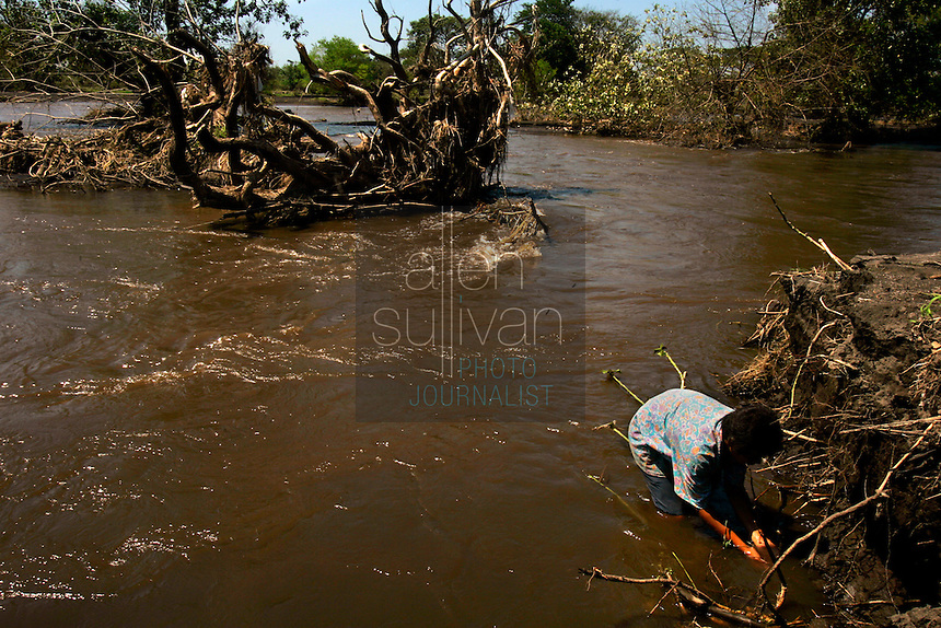 A boy catches shrimp for fun in the Chiguate River. Torrential rains associated with Hurricane Stan inundated parts of Central America in early October, causing flooding, mudslides and death across western Guatemala. Contamination from mud and chemicals from upstream killed the large fish in the river, locals said, and shrimp are the only food source in it now.<br />