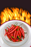Bright red chilli peppers in a white bowl with background flames to show the concept of the heat of the chillis