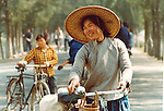 Lady pushing her bike.  Pictures taken in Canton China in 1977 at the time of the cultural revolution.