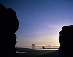 Cape Sebastian State Park Southern Oregon Coast along Highway 101 at sunset low tide with woman riding horse silhouetted and rock formations Oregon State USA